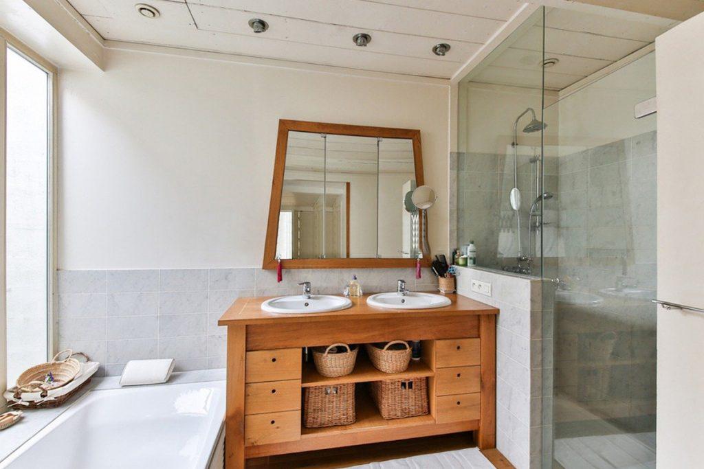 Baño con mueble de madera y plato de ducha con mampara