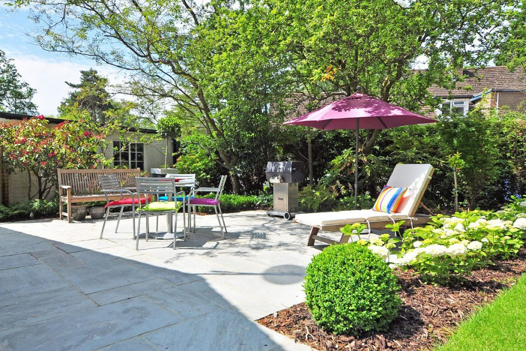 Jardin de casa con tumbona mesas y sillas