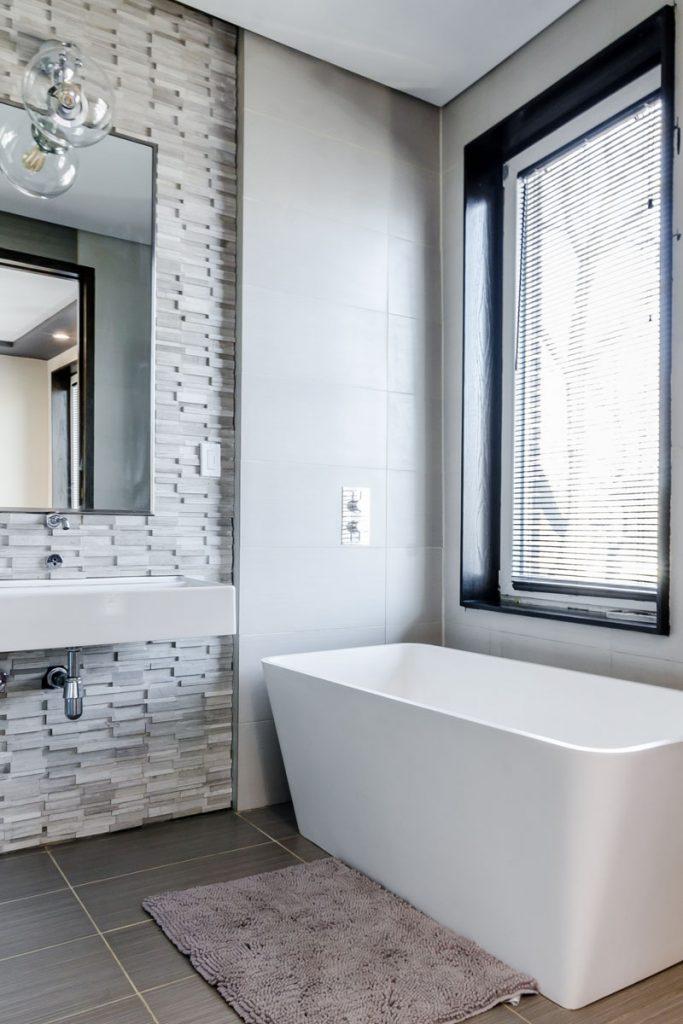 baño minimalista con gran bañera y pared de ladrillo