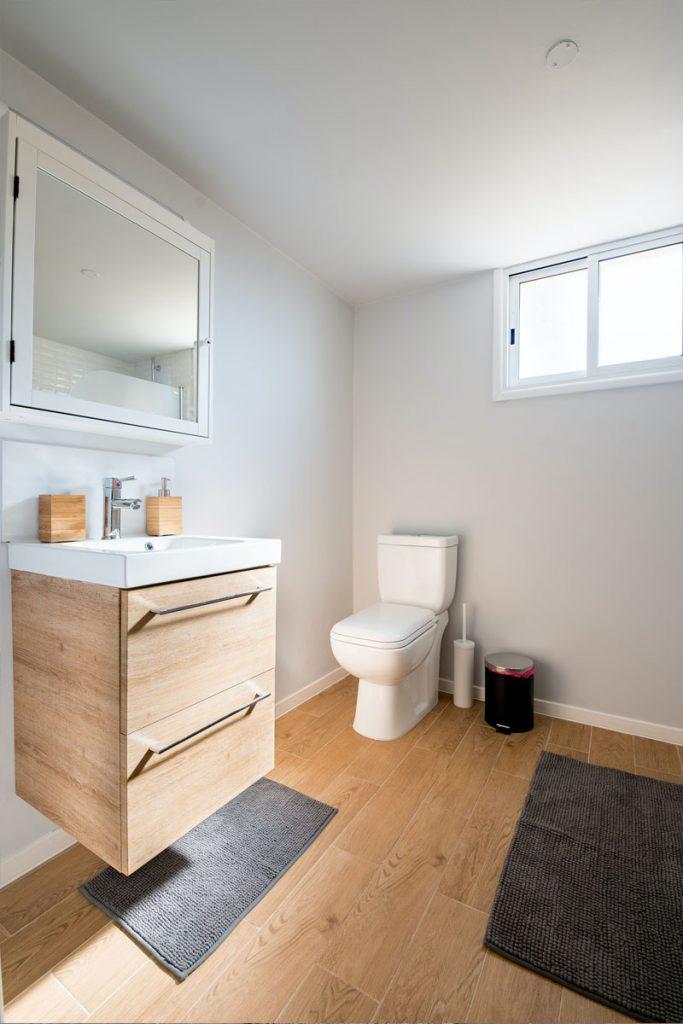 baño minimalistas con suelo de madera y alfombras grises