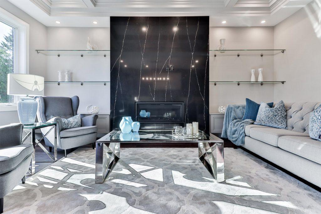 salon minimalista con sillones azules y gran chimenea de marmol en el centro