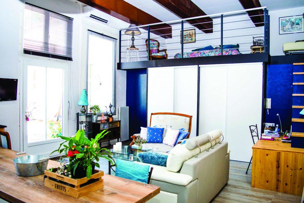 Salon de estilo nautico en color azul y blanco con vigas de madera en el techo