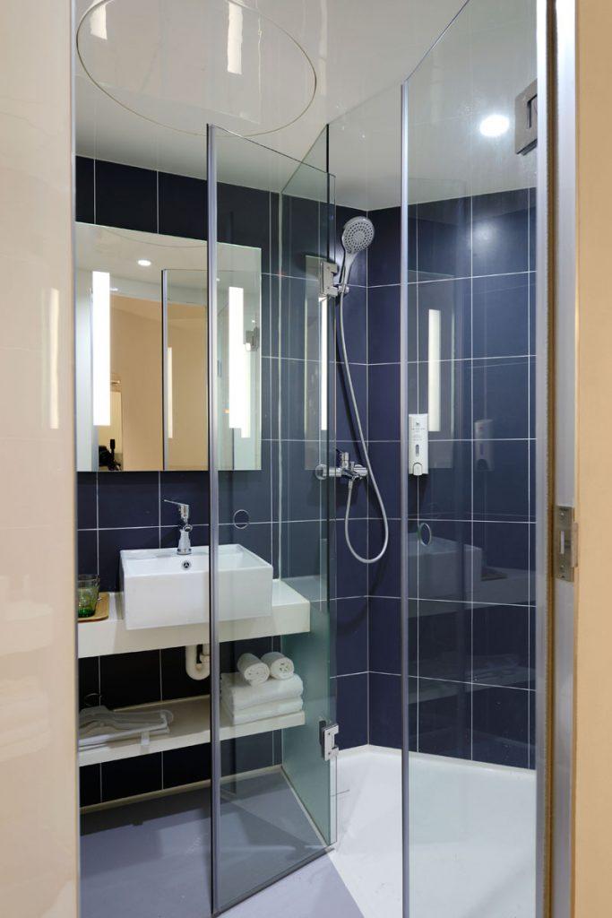 baño ducha de estilo marinero con losetas azules y suelo blanco