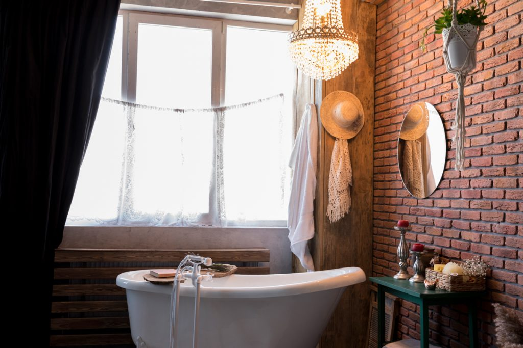 baño estilo bohemio industrial con bañera pequeña y paredes de ladrillo