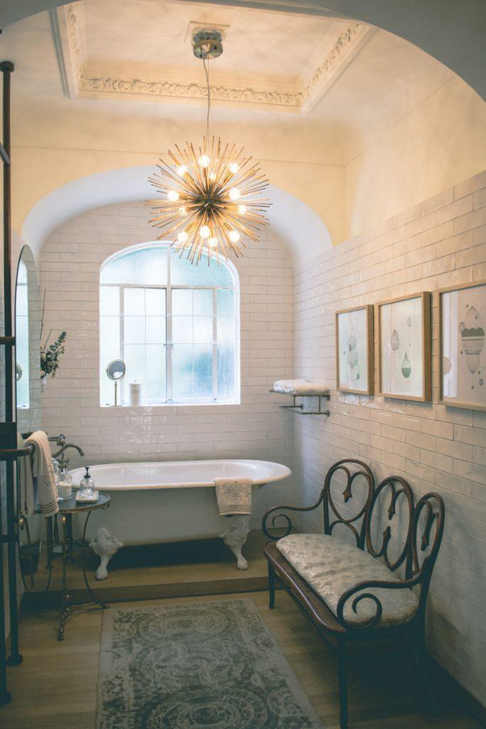 baño industrial con bañera blanca y lampara de pinchos
