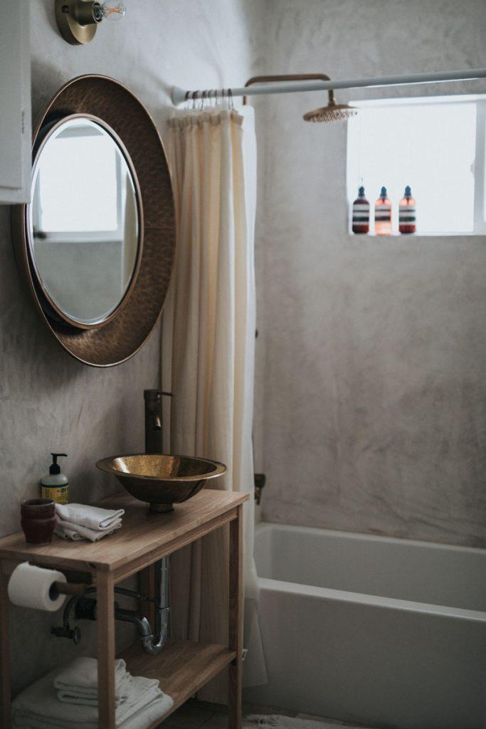 baño industrial con lavabo y espejo de cobre