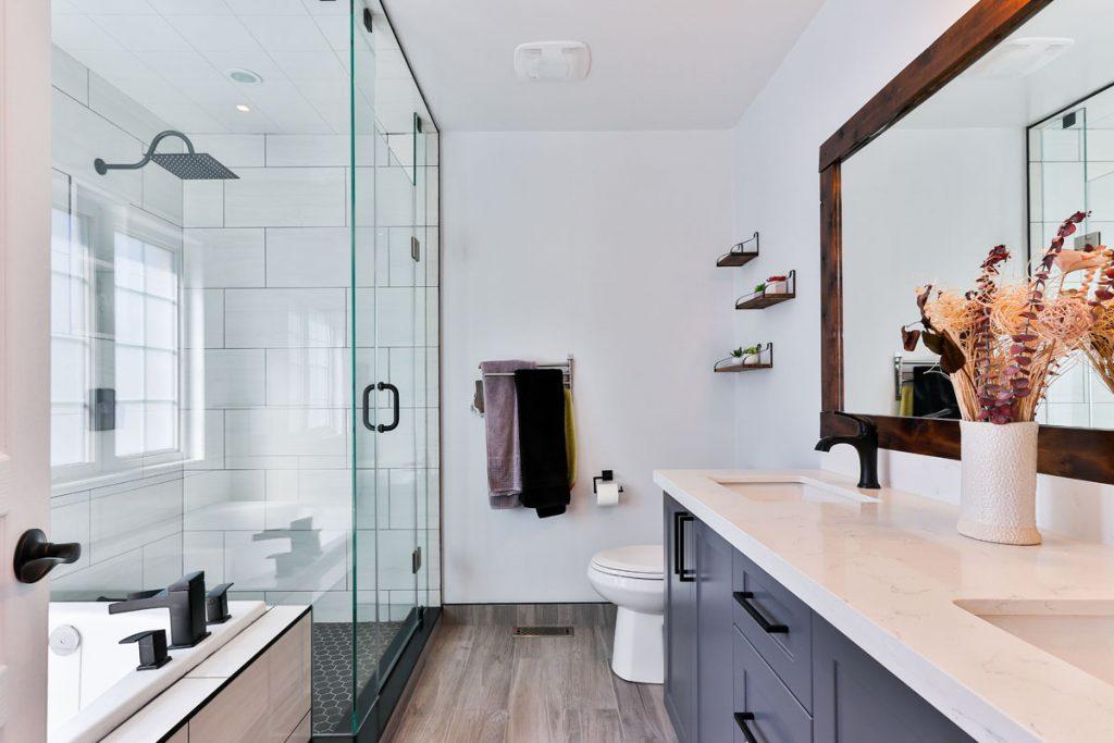 baño moderno con lavabo azul y plato de ducha con pared de ladrillos