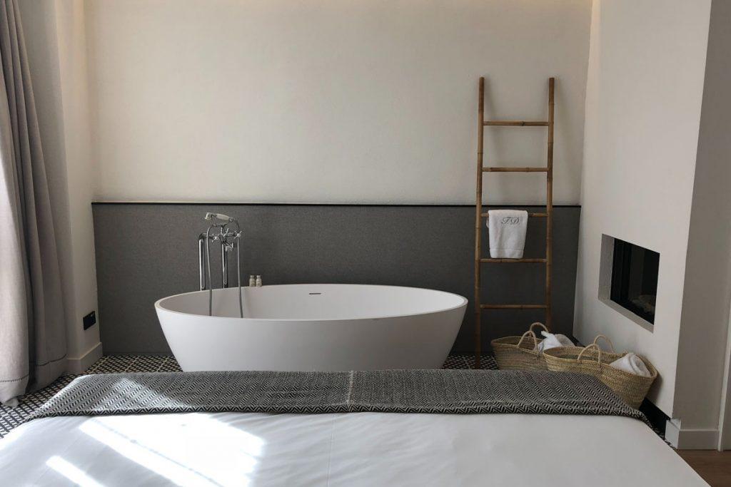baño moderno gris con gran bañera blanca y una escalera decorativa