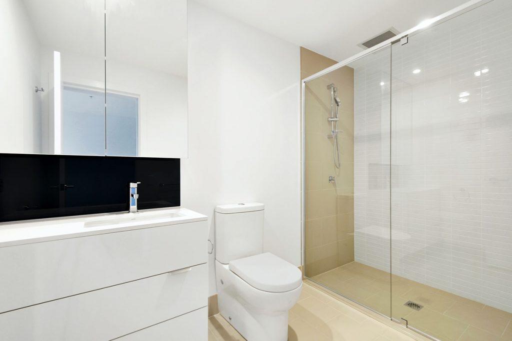 baño moderno minimalista con plato de ducha y mampara de cristal