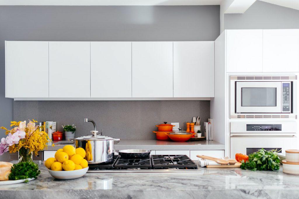 cocina moderna con muebles blancos e isleta de marmol