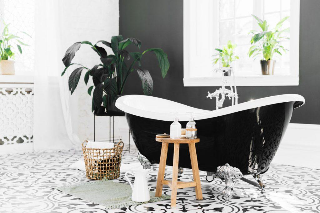 cuarto de baño boho chic minimalista con bañera negra y plantas