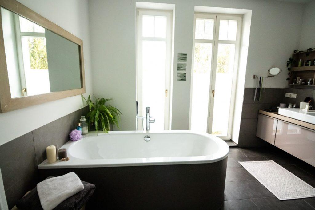 cuarto de baño moderno con suelo negro y gran bañera en el centro