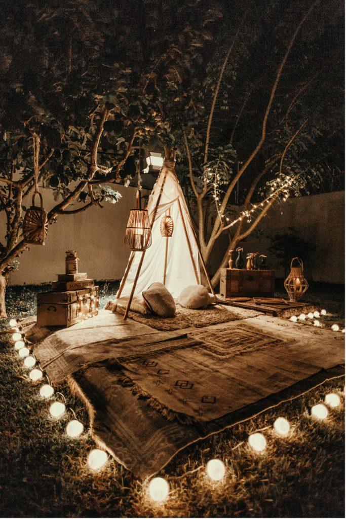 decoracion jardin bohemia con alfombra velas y tienda de campaña