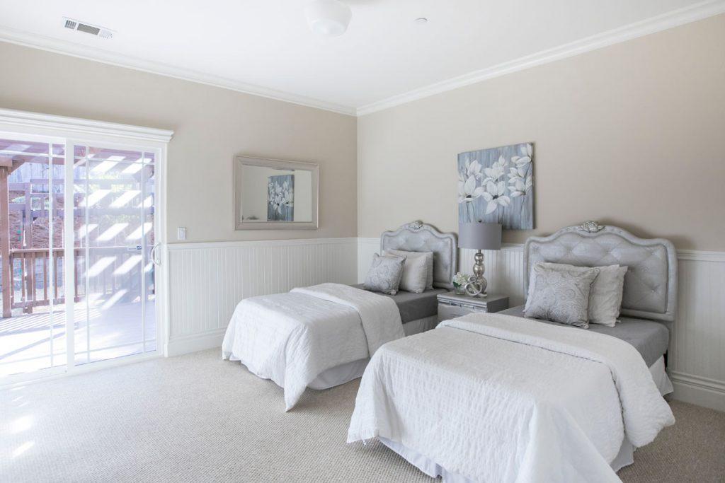 habitacion de estilo clasico moderno con dos camas y decoracion en tonos blancos y crema
