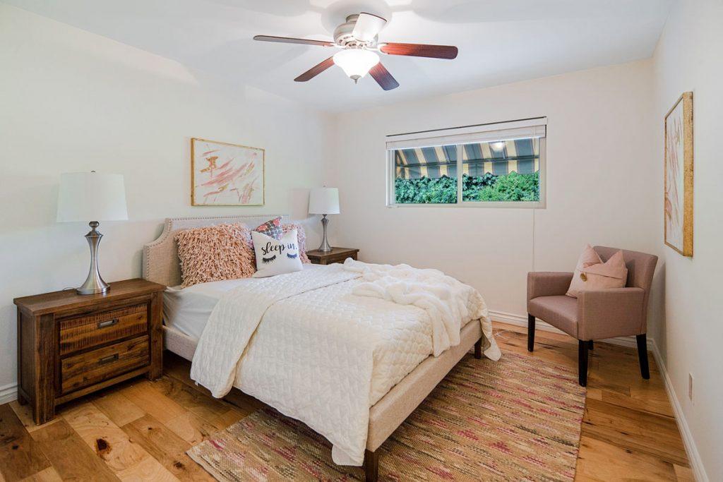 habitacion rustica sencilla con suelo de madera y ventilador