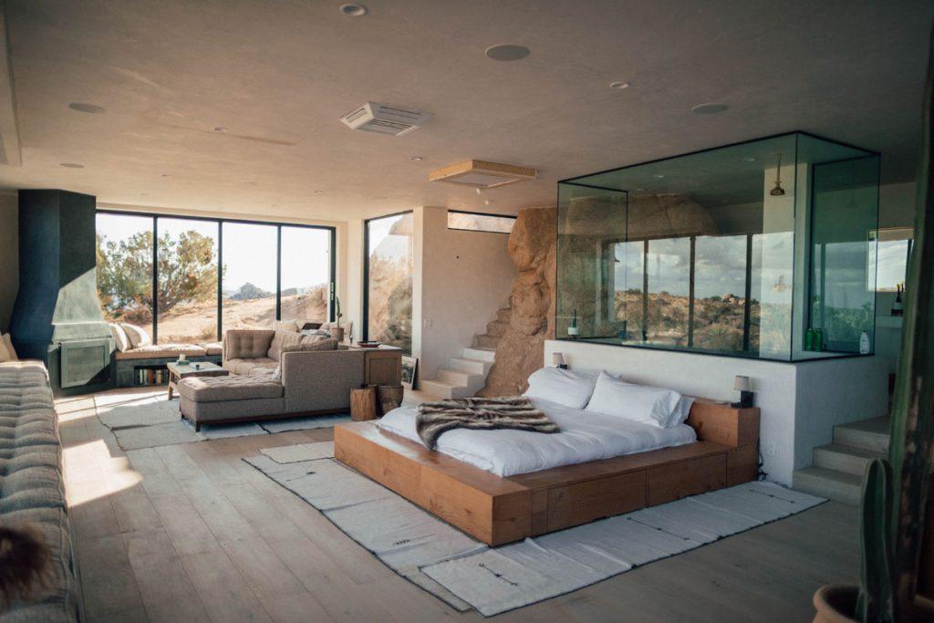 loft industrial diafano con cama salon y una gran roca integrada en la decoracion