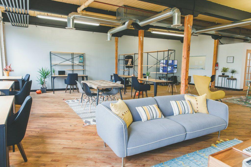 piso tipo loft con suelo de madera tuberias vistas en el techo y muebles de color azul