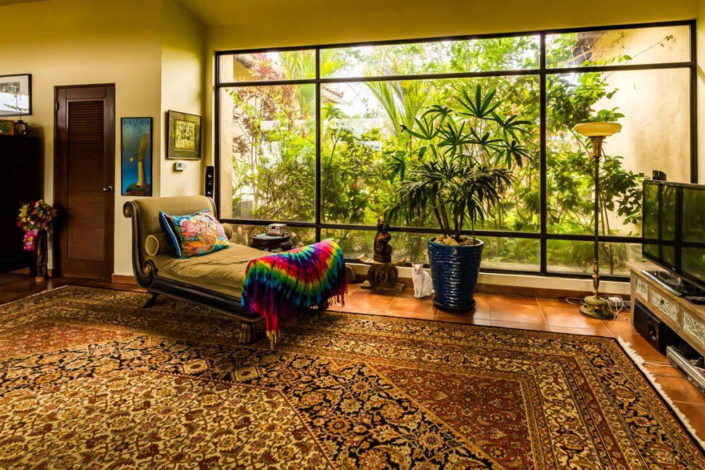 sala de estar estilo bohemio minimalista con cama etnica gran ventanal y enorme alfombra