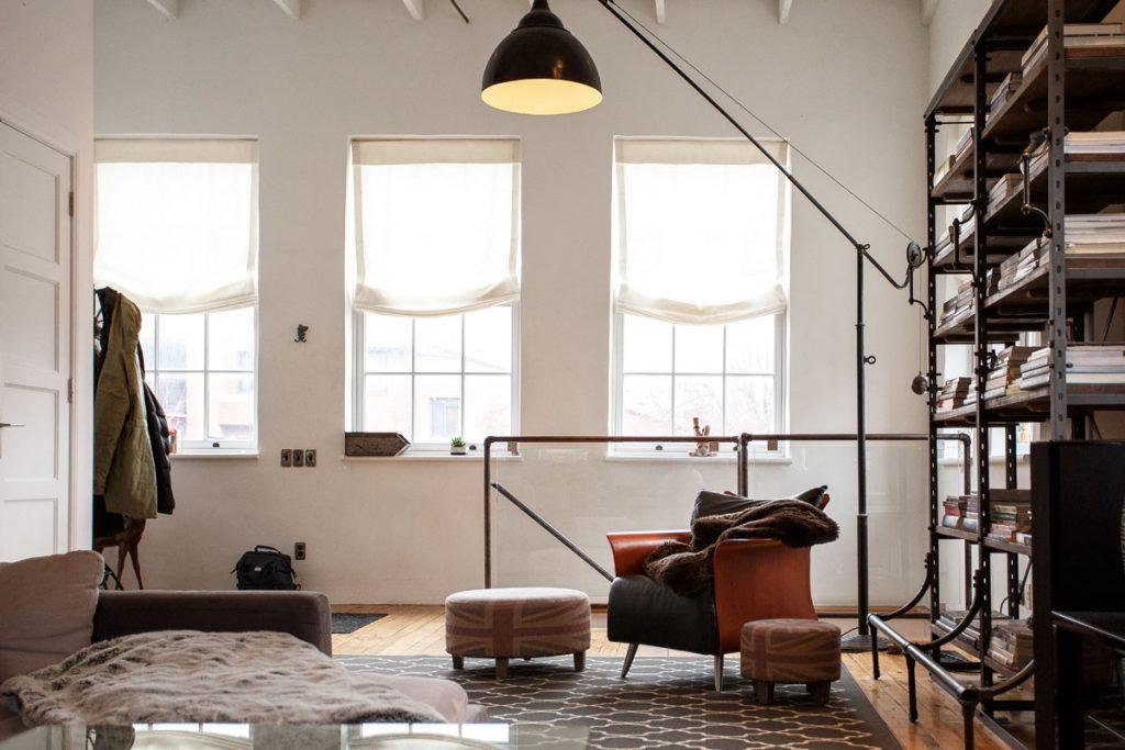 salon de casa loft bien iluminada con sillones y estanteria de metal