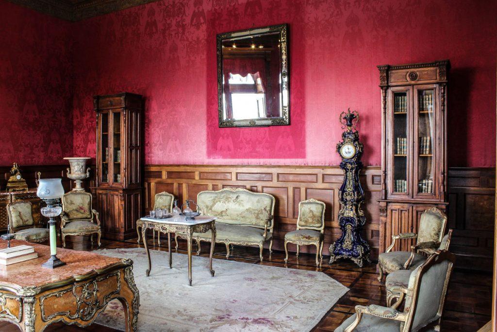 salon de estilo clasico antiguo con muebles viejos y paredes en rojo