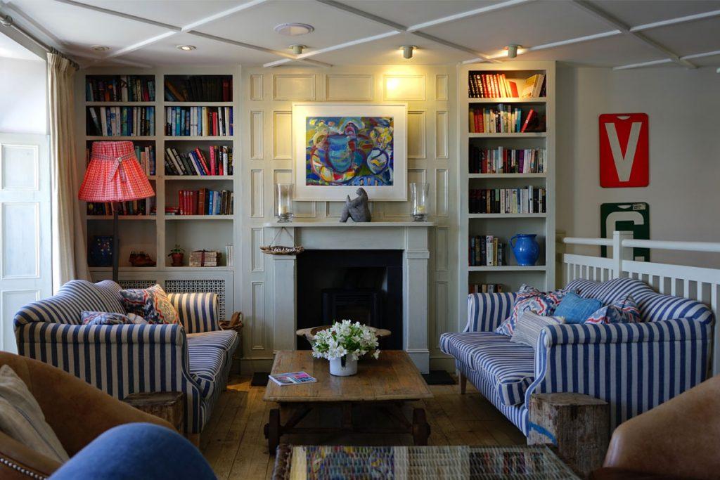 salon de estilo maritimo con estateria de libros y sofas a rayas blancas y azules