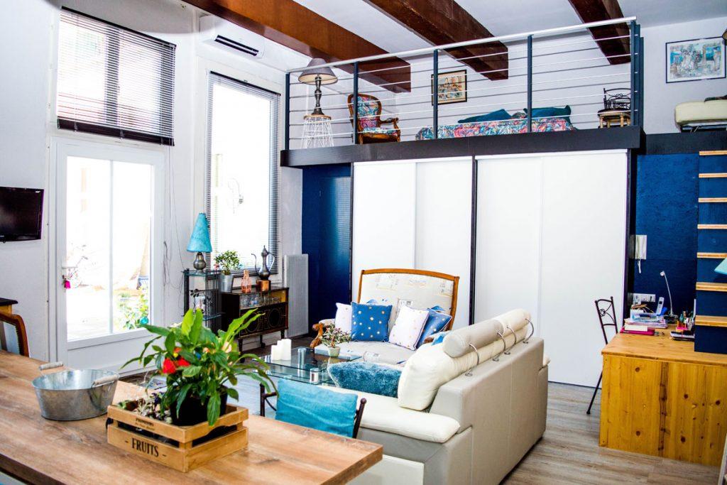 salon loft industrial con vigas en el techo y colores blancos y azules