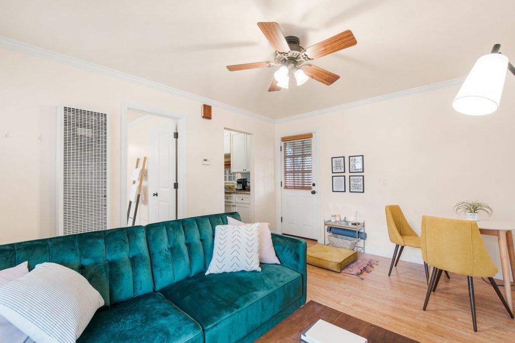 sala de estar con decoracion eclectica con sillon color turquesa y ventilador en el techo